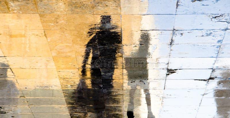 Siluetas borrosas de la sombra de la reflexión de un hombre y de un muchacho que caminan en una calle mojada en un día de verano  imagen de archivo