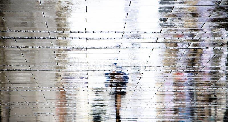Siluetas borrosas de la sombra de la reflexión de una mujer que camina solamente en la lluvia del verano imagenes de archivo