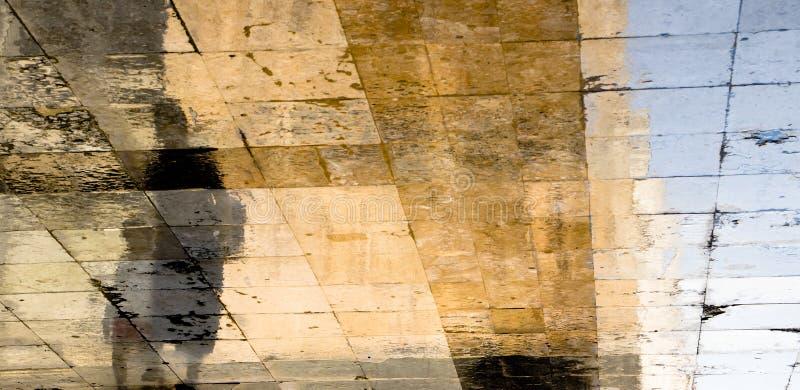 Siluetas borrosas de la sombra de la reflexión de una mujer y de un niño que caminan en una calle mojada en un día de verano sole fotografía de archivo libre de regalías