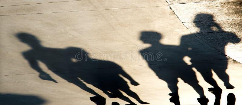 Siluetas borrosas de las sombras de la gente joven que camina en puesta del sol del verano imagen de archivo