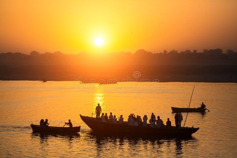 Siluetas de barcos con los peregrinos durante puesta del sol en el río Ganges santo, Varanasi fotos de archivo libres de regalías