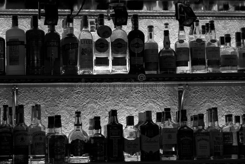 Siluetas de botellas con los templos del alcohol de la culpabilidad en un estante en una barra del club nocturno fotografía de archivo