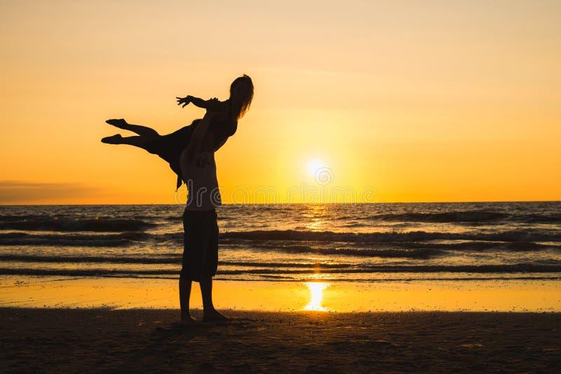 Siluetas de dos bailarines que hacen la acrobacia en la puesta del sol fotografía de archivo libre de regalías
