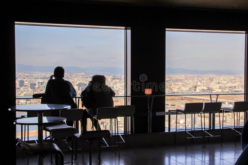 Siluetas de dos hombres que se sientan por la ventana grande en fondo de la vista panorámica de Osaka foto de archivo libre de regalías