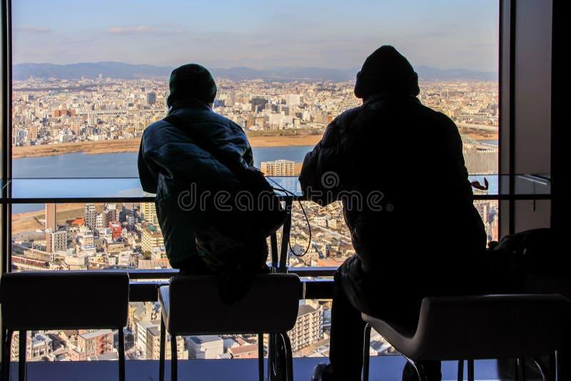Siluetas de dos hombres que se sientan por la ventana grande en fondo de la vista panorámica de Osaka imagen de archivo