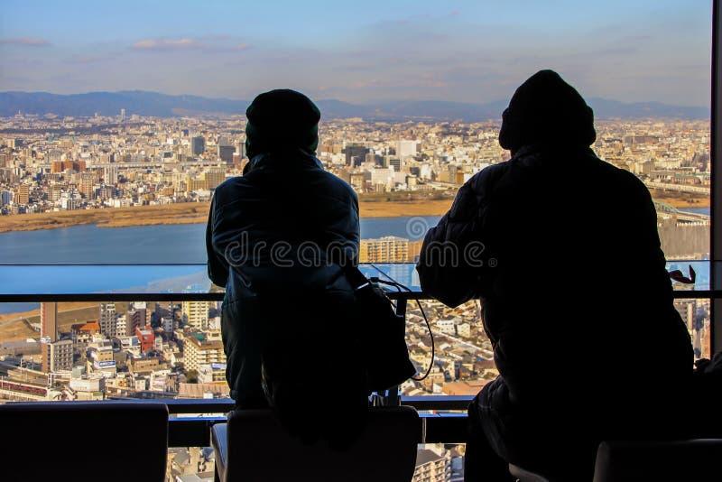 Siluetas de dos hombres que se sientan por la ventana grande en fondo de la vista panorámica de Osaka foto de archivo