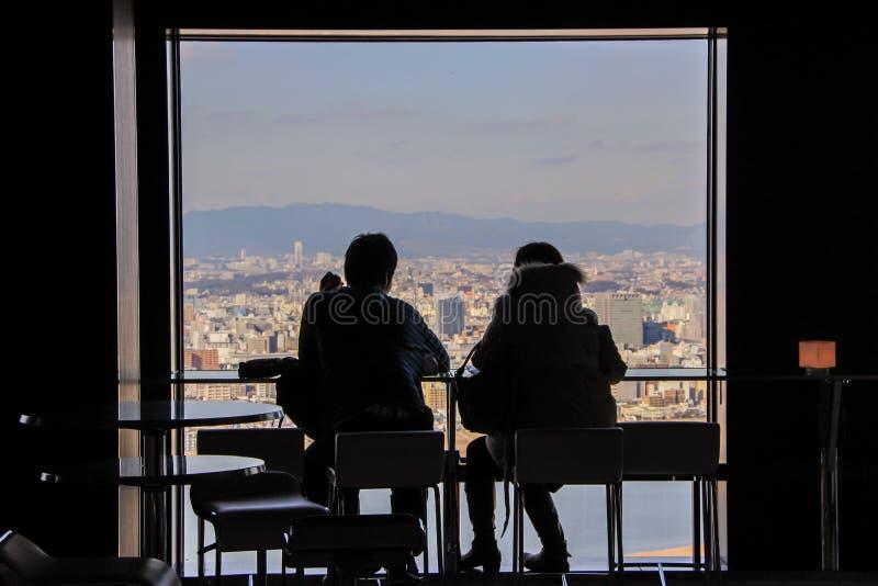 Siluetas de dos hombres que se sientan por la ventana grande en fondo de la vista panorámica de Osaka imágenes de archivo libres de regalías