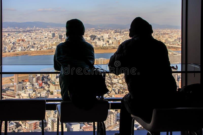 Siluetas de dos hombres que se sientan por la ventana grande en fondo de la vista panorámica de Osaka fotos de archivo libres de regalías