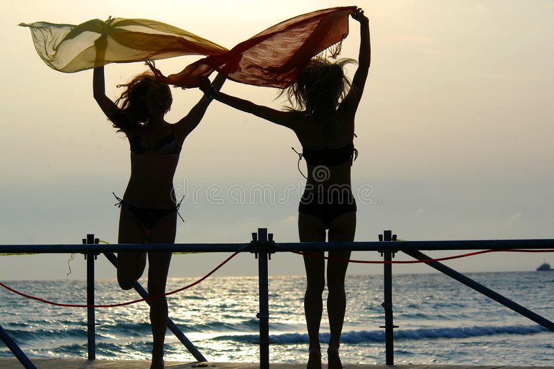Siluetas de dos muchachas que bailan con las bufandas imagen de archivo