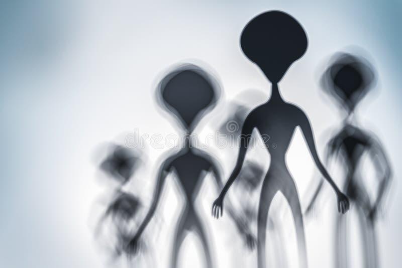 Siluetas de extranjeros fantasmag?ricos y de la luz brillante encendido detr?s de ellos imagen de archivo