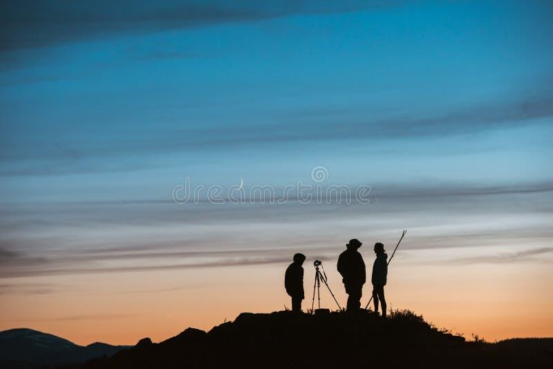 Siluetas de fotógrafos contra el cielo de la puesta del sol foto de archivo libre de regalías