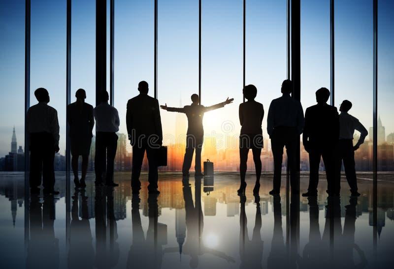 Siluetas de hombres de negocios en un edificio de oficinas fotografía de archivo