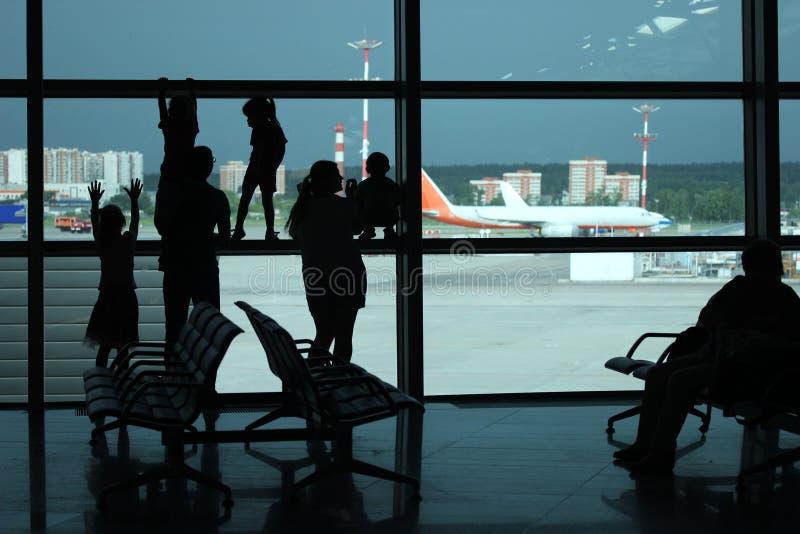 Siluetas de la familia joven que se colocan en la ventana y la mirada en la tira del aeropuerto con los aeroplanos y esperar su fotografía de archivo