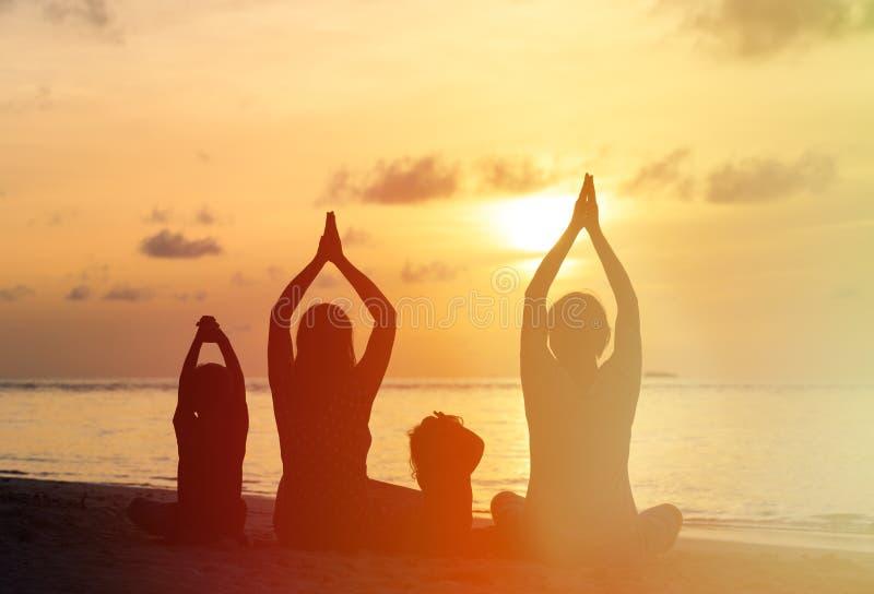Siluetas de la familia que hacen yoga en la puesta del sol foto de archivo