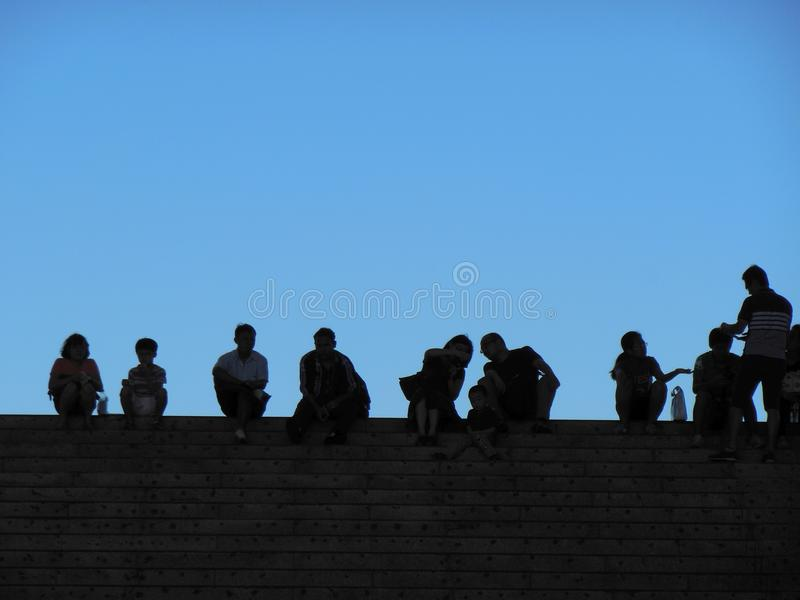 Siluetas de la gente de ciudad al aire libre contra el cielo azul fotografía de archivo