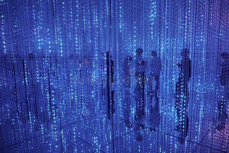 Siluetas de la gente detrás de una cortina de guirnaldas azules eléctricas Espejos del piso imagen de archivo