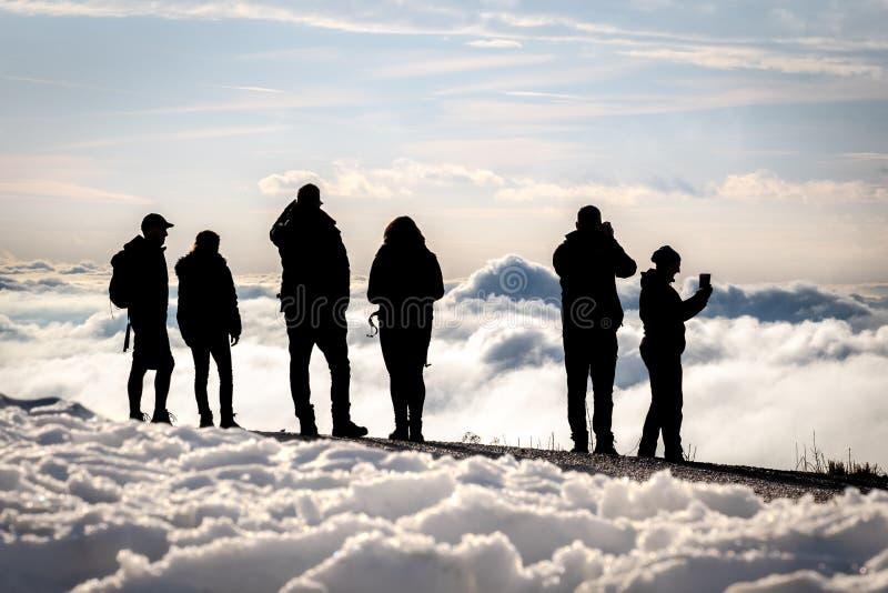 Siluetas de la gente en el pico de montaña foto de archivo