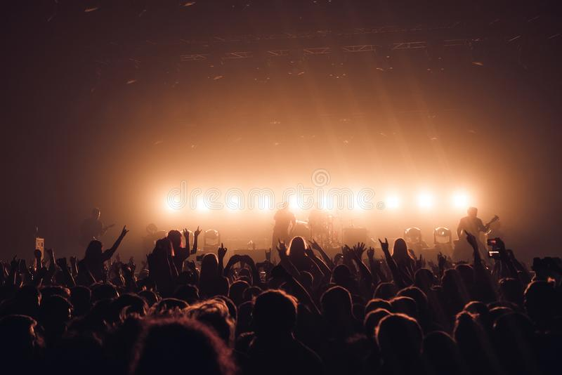 Siluetas de la gente en un brillante en el concierto de rock del estallido delante de la etapa Manos con los cuernos del gesto Es imagen de archivo libre de regalías