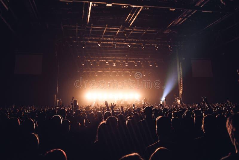 Siluetas de la gente en un brillante en el concierto de rock del estallido delante de la etapa Manos con los cuernos del gesto Es foto de archivo libre de regalías