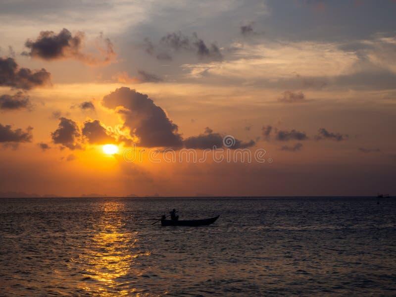 Siluetas de la gente en un kajak en los rayos del sol poniente contra la perspectiva de las nubes imagen de archivo libre de regalías