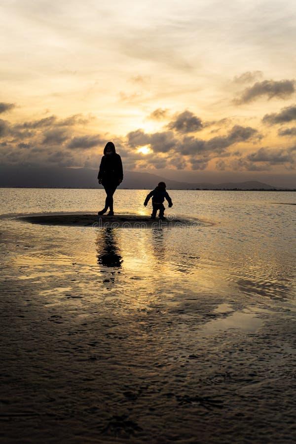 Siluetas de la gente irreconocible en la playa en la puesta del sol imagen de archivo libre de regalías