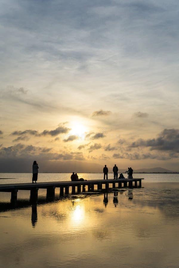 Siluetas de la gente irreconocible en un embarcadero en la puesta del sol imagenes de archivo