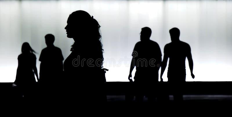 Siluetas de la gente joven que camina en la falta de definición de movimiento en cerca foto de archivo