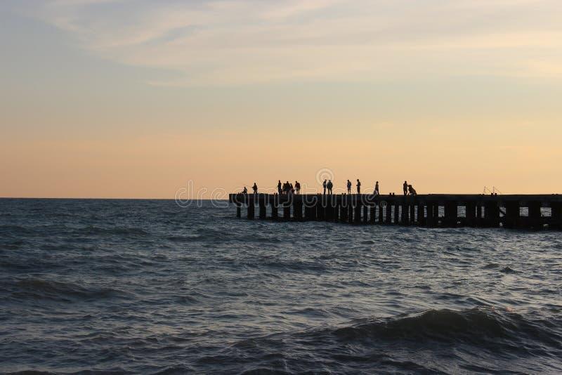 Siluetas de la gente, probablemente pescadores en el embarcadero en el mar imágenes de archivo libres de regalías