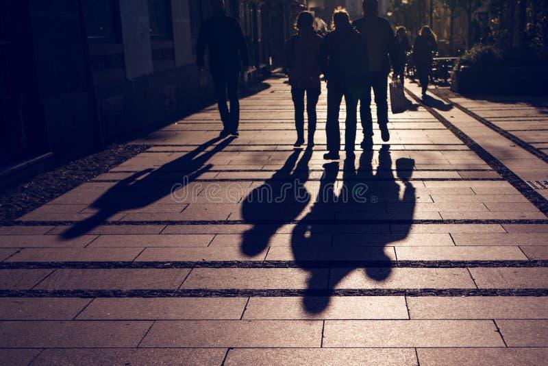 Siluetas de la gente que camina en la calle de la ciudad imágenes de archivo libres de regalías