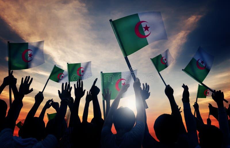 Siluetas de la gente que sostiene la bandera de Argelia fotografía de archivo