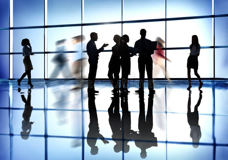Siluetas de la gente que trabaja en un edificio de oficinas imagen de archivo