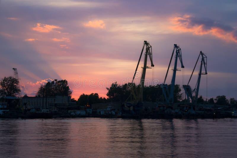 Siluetas de la grúa en la puesta del sol imágenes de archivo libres de regalías