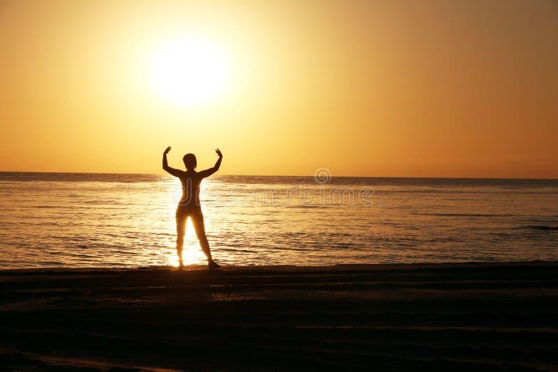 Siluetas de la muchacha con las manos aumentadas contra un fondo de una salida del sol imágenes de archivo libres de regalías