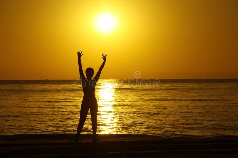 Siluetas de la muchacha con las manos aumentadas contra un fondo de una salida del sol en la costa de mar fotos de archivo libres de regalías