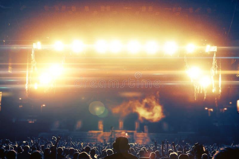 Siluetas de la muchedumbre del concierto delante de una etapa brillante imágenes de archivo libres de regalías