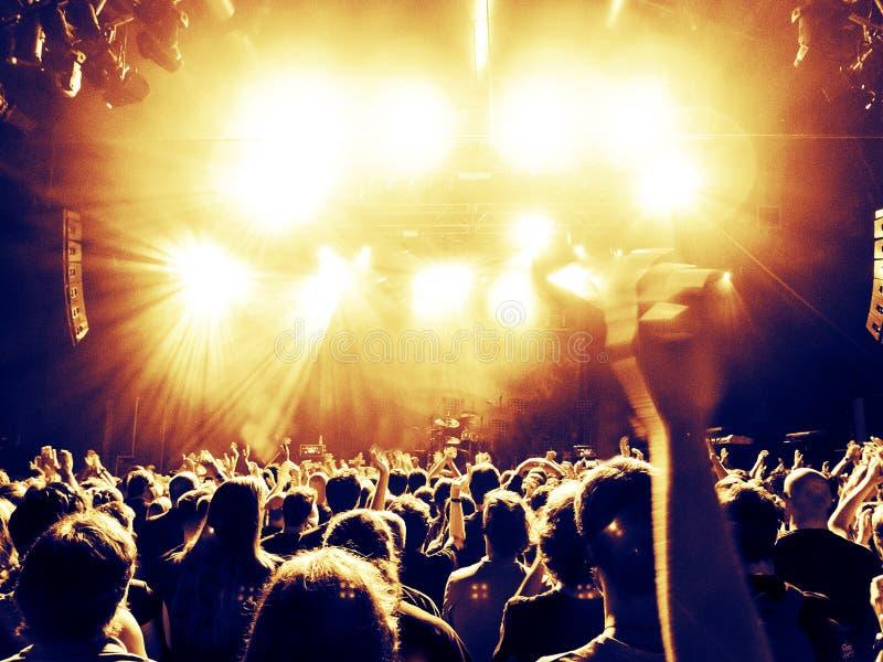Siluetas de la muchedumbre del concierto delante de una etapa brillante fotos de archivo