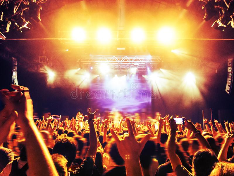Siluetas de la muchedumbre del concierto delante de una etapa brillante imagen de archivo