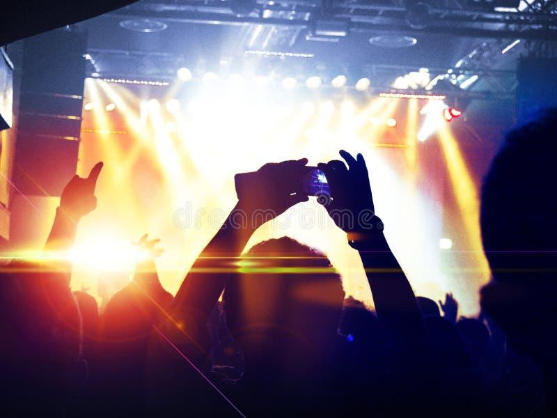 Siluetas de la muchedumbre del concierto delante de una etapa brillante fotografía de archivo