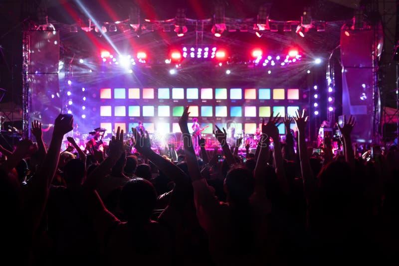 Siluetas de la muchedumbre, grupo de personas, animando en concierto de la m?sica en directo delante de luces coloridas de la eta imagenes de archivo