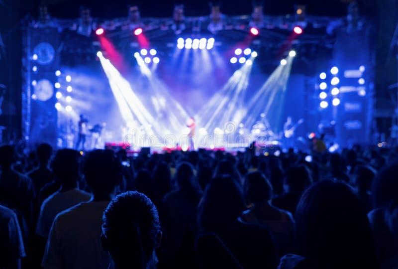Siluetas de la muchedumbre, grupo de personas, animando en concierto de la m?sica en directo delante de luces coloridas de la eta imagen de archivo libre de regalías