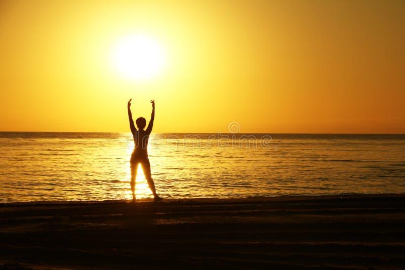 Siluetas de la mujer con las manos aumentadas contra un fondo de una salida del sol en la costa de mar imagen de archivo libre de regalías