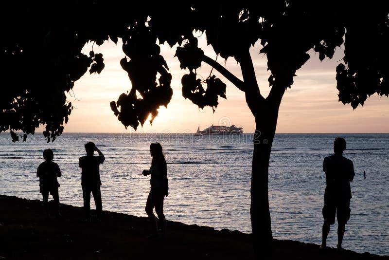 Siluetas de la puesta del sol por el mar imagenes de archivo