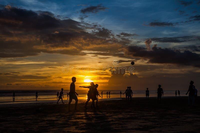 Siluetas de la puesta del sol que juegan al fútbol el Brasil de la playa de Altinho Futebol imagen de archivo