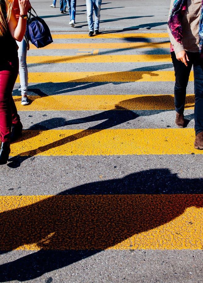 Siluetas de la sombra que camina de la gente en el paso de peatones de la calle de la ciudad imagenes de archivo