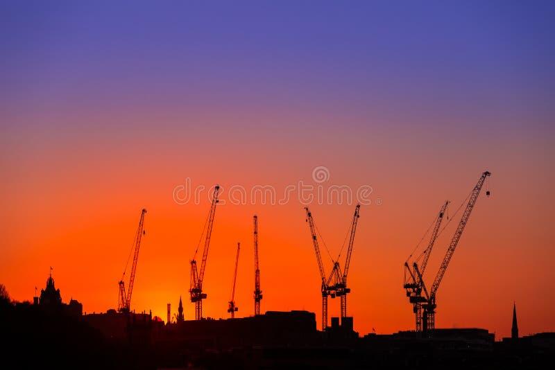 Siluetas de las grúas de construcción en un backgr del cielo de la puesta del sol del paisaje urbano imágenes de archivo libres de regalías