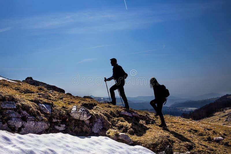 Siluetas de los caminantes que caminan en las montañas foto de archivo