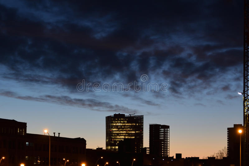 Siluetas de los edificios en la ciudad en la noche Nubes oscuras en la salida del sol foto de archivo libre de regalías