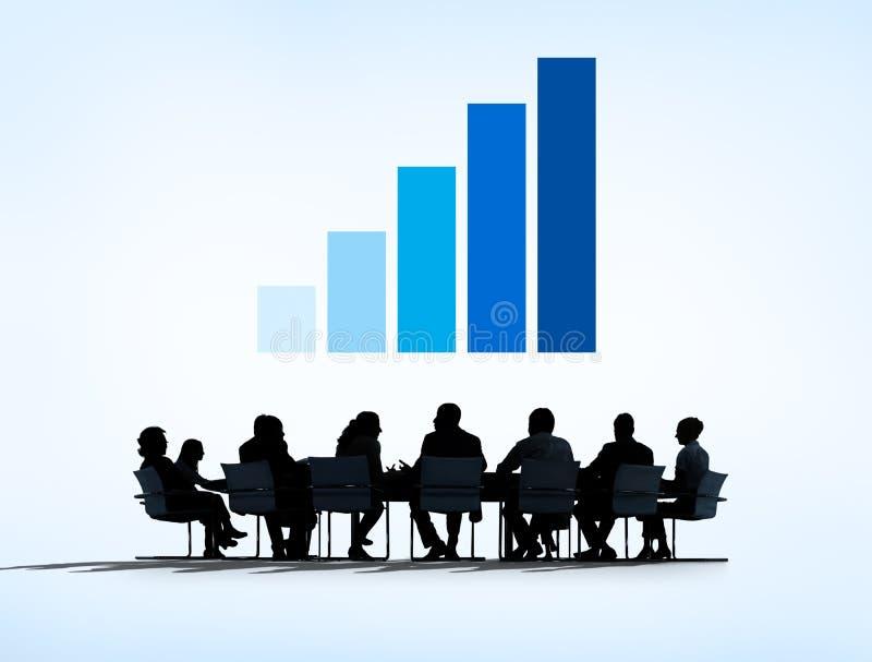 Siluetas de los hombres de negocios que tienen una reunión y un gráfico arriba imagen de archivo libre de regalías