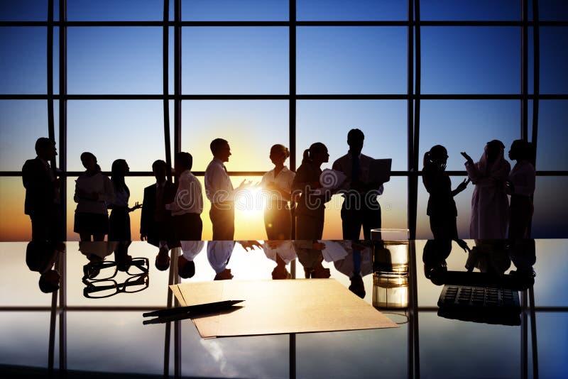 Siluetas de los hombres de negocios que trabajan en sala de juntas imagen de archivo
