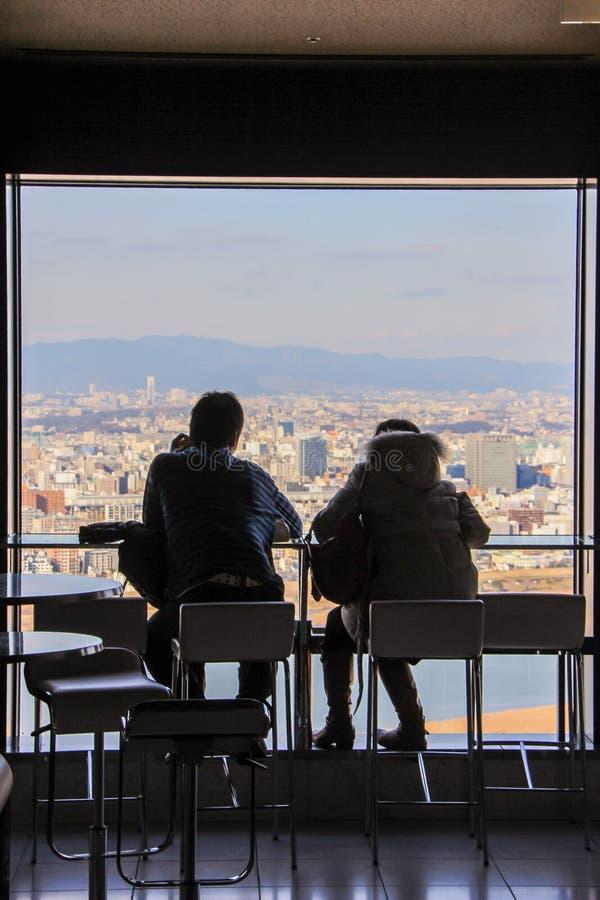 Siluetas de los hombres que se sientan por la ventana grande en fondo de la vista panorámica de Osaka imagen de archivo